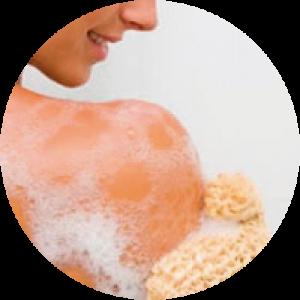 Mujer exfoliandose con guante de crin