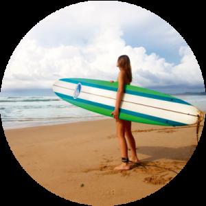 Chica en una playa con una tabla de surf para explicar la depilación láser con la exposición solar