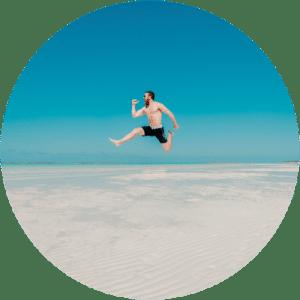 Hombre saltando en una playa con el torso y piernas depiladas