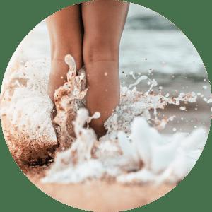 Mujer en la playa con las piernas depiladas y rasuradas