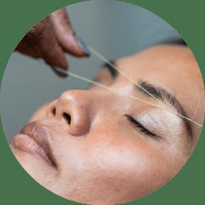 Mujer depilándose la ceja con hilo